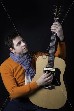 Мужчина позирует с гитарой