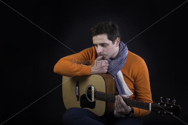 Мужчина позирует с гитарой на черном фоне