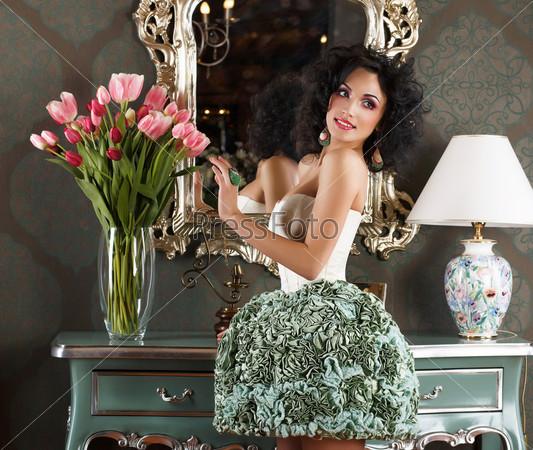 Красивая гламурная женщина в ретро-интерьере с цветами. Отражение