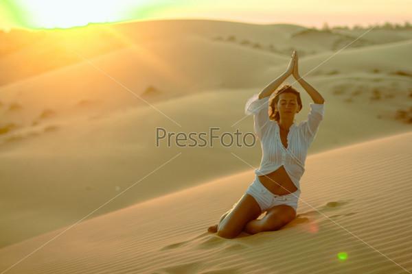 Красивая женщина медитирует в пустыне