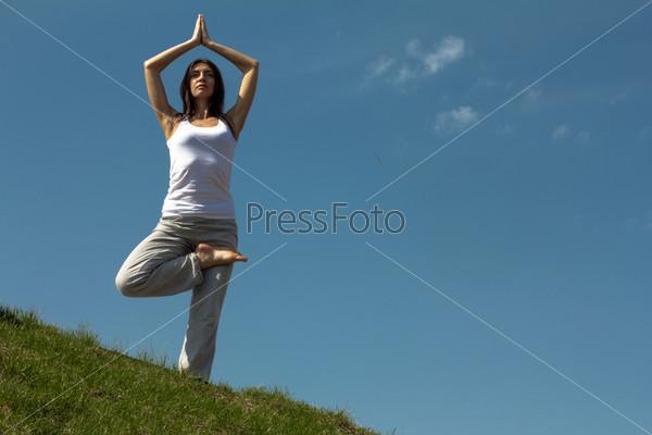 Стройная молодая женщина занимается йогой