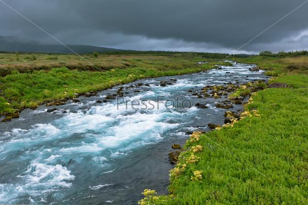 Летний исландский пейзаж с бушующей рекой