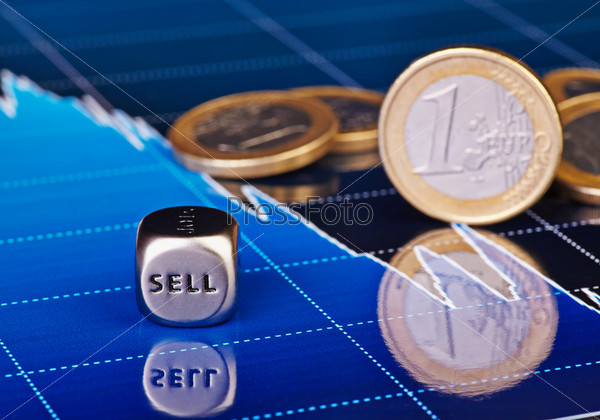 Кубик со словом продажа, один евро и финансовые индикаторы как фон. Выборочный фокус