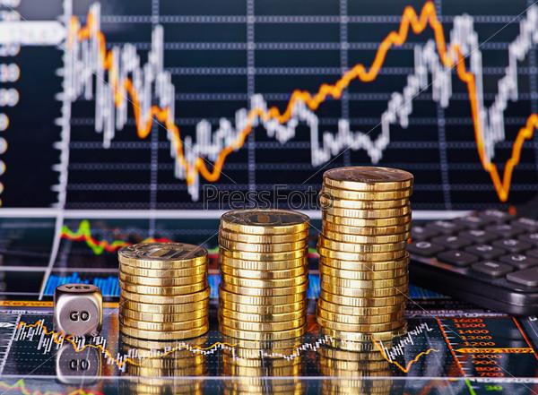 Фотография на тему Восходящий график, стопки монет, кубик со словом GO и калькулятор на финансовых графиках состояния запасов. Выборочный фокус