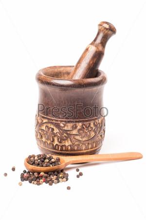 Перец с деревянной ложкой на белом фоне