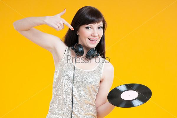 Улыбающаяся женщина DJ с виниловой пластинкой, желтый фон