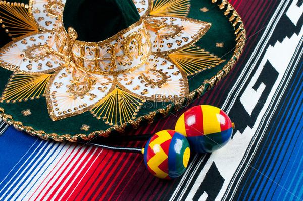 Фотография на тему Традиционные мексиканские сомбреро, маракасы и разноцветное пончо