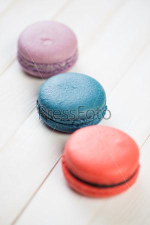 Разноцветные французские макароне на деревянных досках