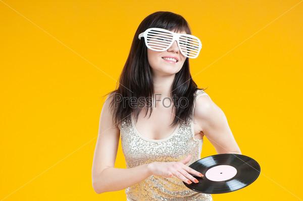 Гламурная девушка DJ с виниловой пластинкой, желтый фон