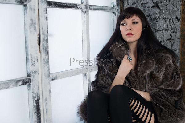 Гламурная молодая женщина позирует на подоконнике