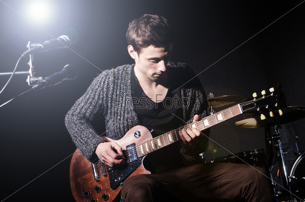 Фотография на тему Мужчина играет на гитаре во время концерта