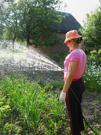 Девушка поливает огород