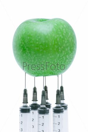 Зеленое яблоко с вставленными шприцами, изолированное на белом фоне