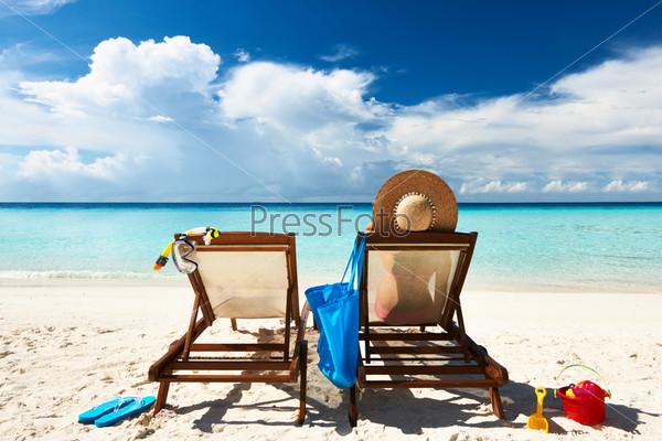 Женщина на тропическом пляже в шезлонге