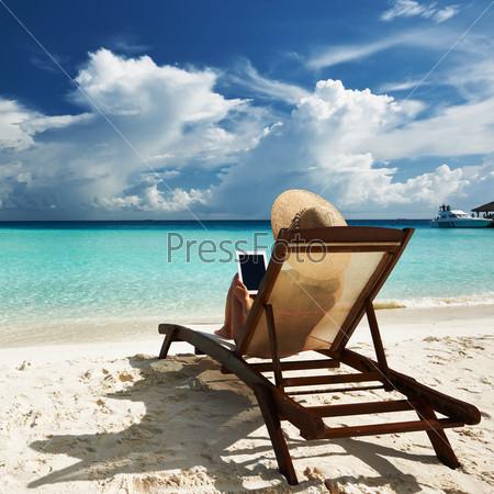 Фотография на тему Женщина на тропическом пляже в шезлонге