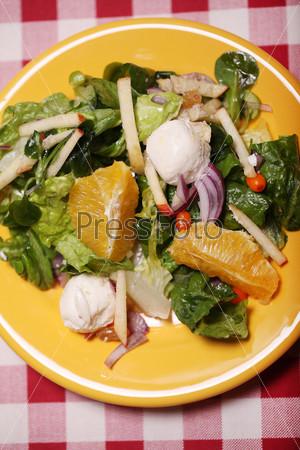Свежий вкусный салат в тарелке на скатерти