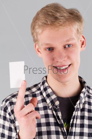 Молодой красивый парень держит пластиковую карточку