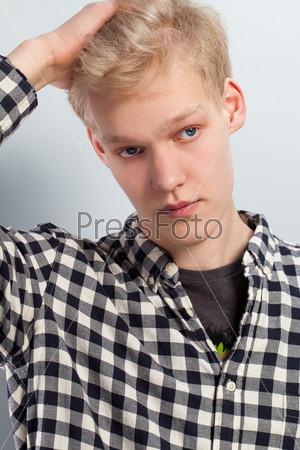 Молодой красивый парень с рукой на голове