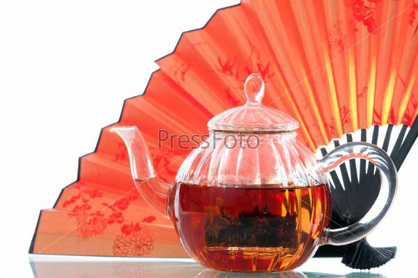 Чайник с зеленым чаем и оранжевый китайский веер на белом фоне
