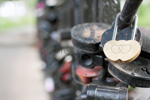 Фотография на тему Золотой замок в форме сердца висит на мосту рядом другими замками
