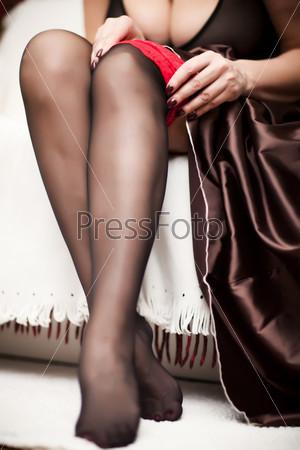 Соблазнительные женские ноги в черных чулках с красными резинками