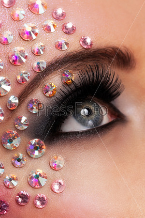 Глаз с макияжем и кристаллами крупным планом