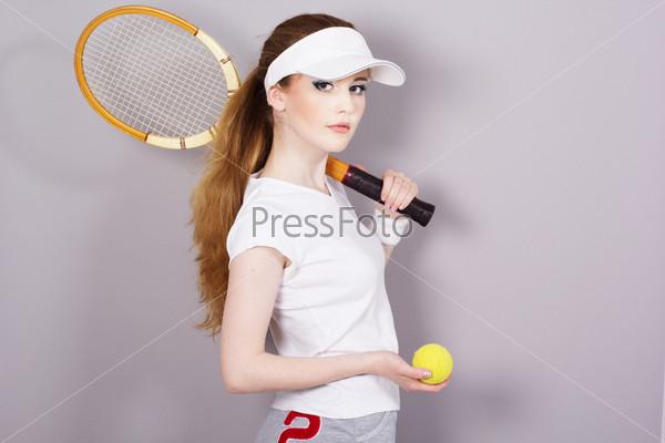 Фотография на тему Молодая девушка с теннисной ракеткой, изолировано на сером