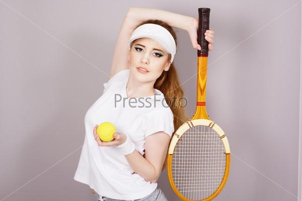 Молодая девушка с теннисной ракеткой, изолировано на сером