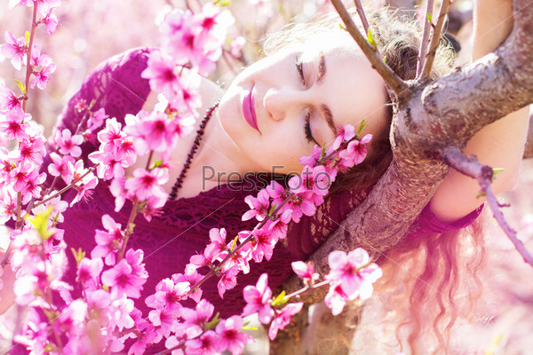 Красивая девушка в розовом цветущем саду