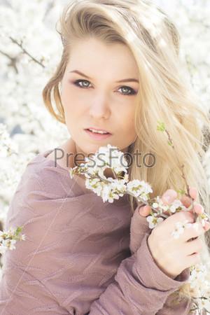 Красивая блондинка в весеннем вишневом саду