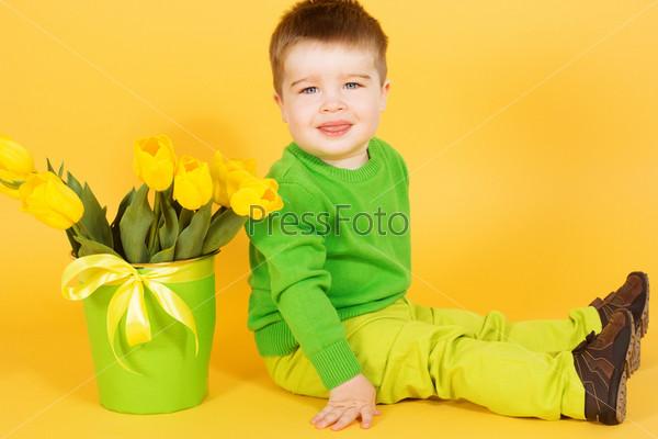 Фотография на тему Маленький мальчик с букетом желтых тюльпанов