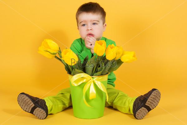 Маленький мальчик с букетом желтых тюльпанов
