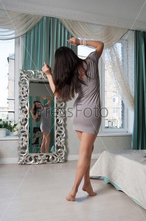 Фотография на тему Женщина в сером платье смотрит в зеркало