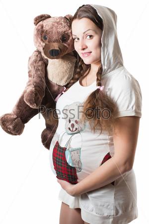 Беременная женщина и плюшевым медведем, изолированная на белом фоне