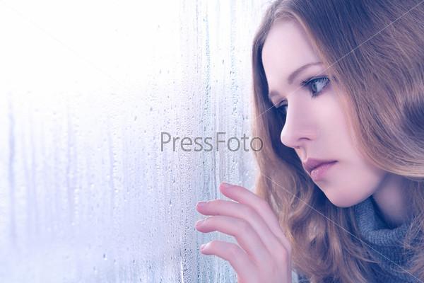 Фотография на тему Девушка грустит у окна в дождь
