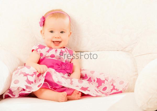 Красивая девочка в розовом платье сидит на диване дома