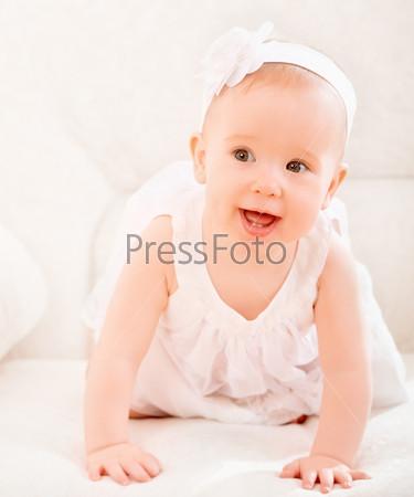 Улыбающаяся милая девочка в белом платье с цветком