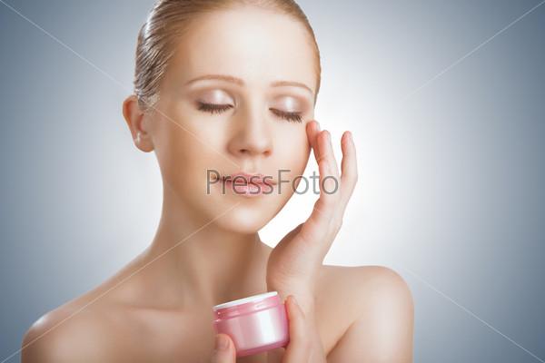 Уход за кожей. Женщина с закрытыми глазами и баночкой крема