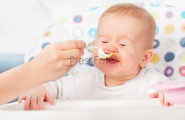 Маь кормит забавного ребенка с ложки