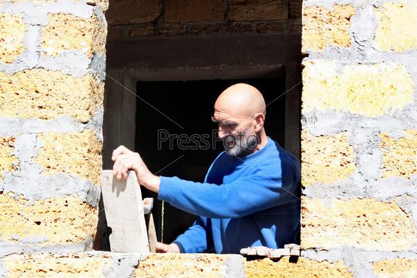 Мужчина в процессе работы на стройке. Горизонтально