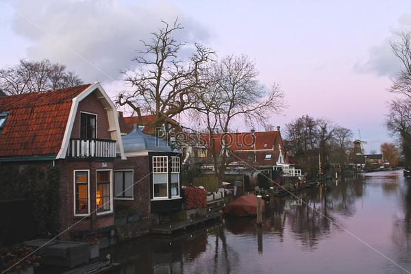 Рождественские огни в домах на реке в голландском городе Ленен. Нидерланды