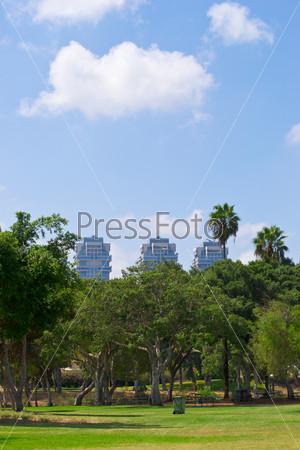 Фотография на тему Современное здание, обрамленное зеленью деревьев и облачное небо