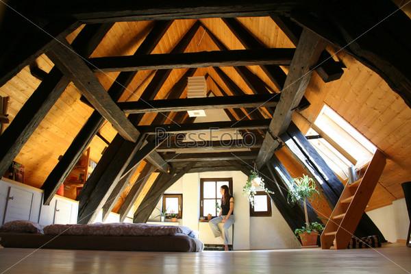 Фотография на тему Мансардная комната с темными деревянными балками