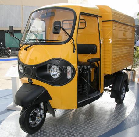 Желтый трехколесный пикап на автомобильной выставке в Дели, Индия