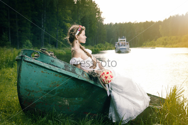 Красивая молодая невеста, сидяша в лодке