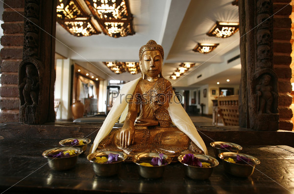Статуя Будды перед зеркалом в лобби отеля