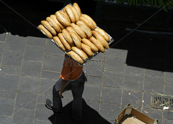 Человек несет буханки хлеба на местном рынке