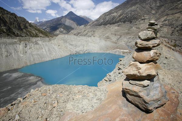 Фотография на тему Стопка мемориальных камней у голубого горного озера, Аннапурна, Непал