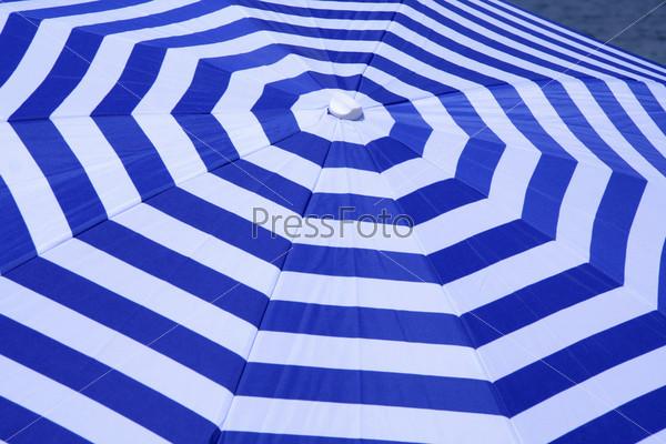Сине-белый полосатый зонт на пляже