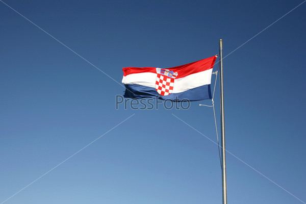 Фотография на тему Хорватский флаг, развивающийся на фоне синего неба